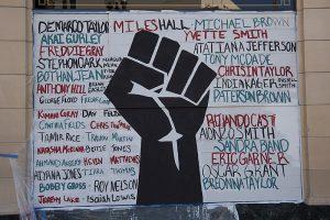 Black Lives Matter. Veggmaleri fra Oakland, California. Maleriet viser en knyttet sort neve og navn på ofre for politivold. Foto: Wikimedia Commons.